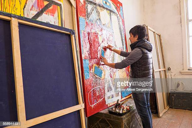Artist drawing on abstract painting in studio