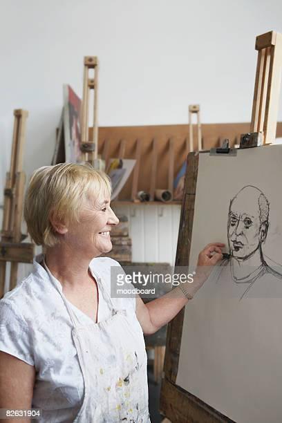 Artist drawing portrait in studio, side view