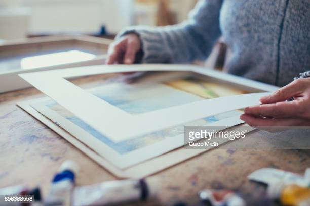 Artist framing a picture.
