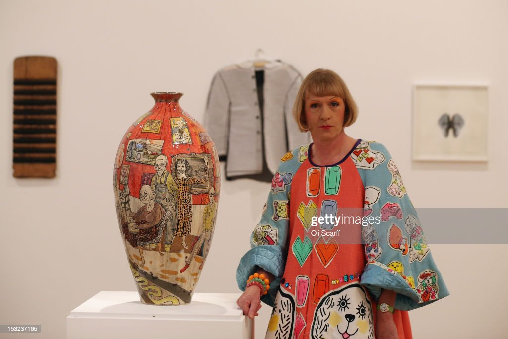 Artist Grayson Perry poses next to his vase entitled 'Bad Portraits of Establishment Figures' in the 'RA Now' exhibition at the Royal Academy on...