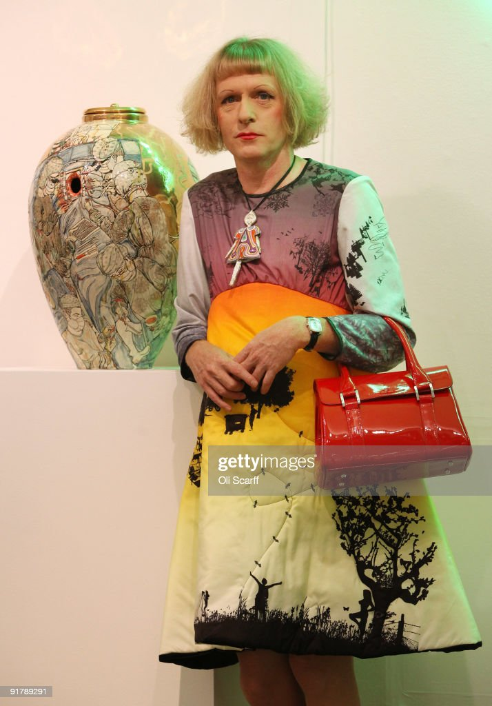 Artist Grayson Perry poses with his artwork 'Urn For The Living' at Sotheby's auction house on October 12 2009 in London England The urn is one of...