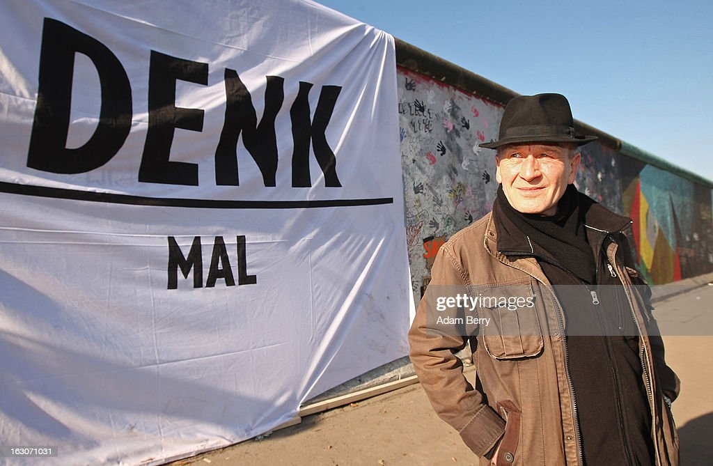 Artist Guenther Schaeffer, who has painted a section of the East Side Gallery, poses in front of a banner reading 'Denk Mal,' a pun in German on the imperative 'Think' and 'Monument, next to the longest remaining portion of the former Berlin Wall on March 4, 2013 in Berlin, Germany. A real estate developer is planning to build a 14-storey apartment building between the East Side Gallery and the Spree River and needs to remove the Wall section in order to allow access to the construction site. Protesters managed to temporarily halt the dismantling of the section on March 1. Critics, including East Side Gallery mural artists and Spree River embankment development opponents, decry the move, citing the importance of the East Side Gallery's status as a protected landmark and a major tourist attraction. The East Side Gallery is approximately 1.3 kilometers long.