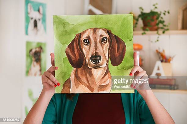 Artist hiding behind aquarelle of a dachshund