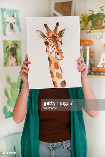 Artist hiding behind aquarelle of a giraffe
