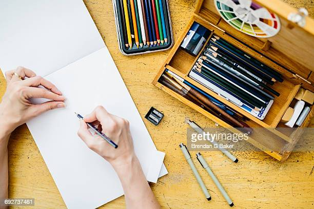 Artist holding pencil, about to start drawing, overhead view