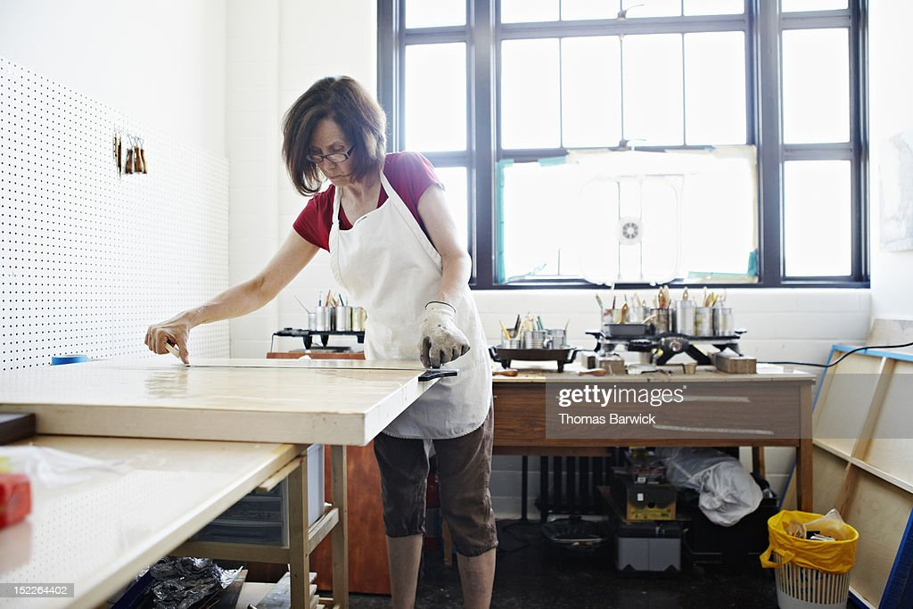 Artist in studio measuring out tape on painting : Stock Photo