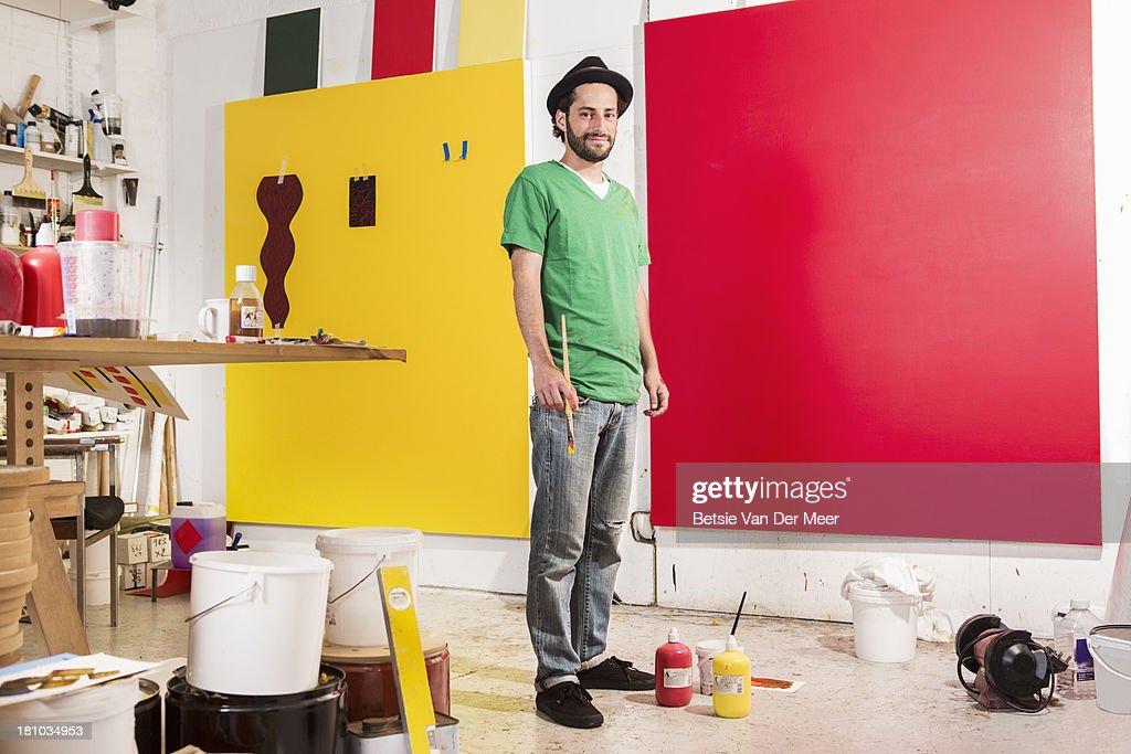 Artist in studio working on painting.