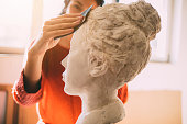 Young sculptor creates sculpture.