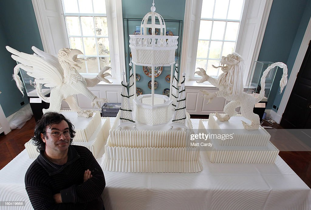 Artist Joan Sallas stands beside a 1.5 metre high folded linen table fountain he is displaying as part of a new exhibition 'Folded Beauty: Masterpieces in Linen', which is opening at the Holbourne Museum on January 31, 2013 in Bath, England. The exhibition of the lost art of linen folding, examples of which would once have graced the dining tables of Kings and Emperors in seventeenth century Europe, will include animals, flowers and even miniature buildings and fountains all made from intricately starched and folded linen. This is the first UK exhibition by the world's leading authority on historic linen folding who has previously exhibited his work across Europe and the USA.