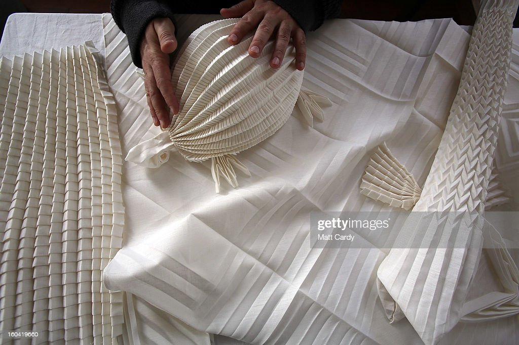 Artist Joan Sallas works on some folded linen for his new exhibition 'Folded Beauty: Masterpieces in Linen', which is opening at the Holbourne Museum on January 31, 2013 in Bath, England. The exhibition of the lost art of linen folding, examples of which would once have graced the dining tables of Kings and Emperors in seventeenth century Europe, will include animals, flowers and even miniature buildings and fountains all made from intricately starched and folded linen. This is the first UK exhibition by the world's leading authority on historic linen folding who has previously exhibited his work across Europe and the USA.