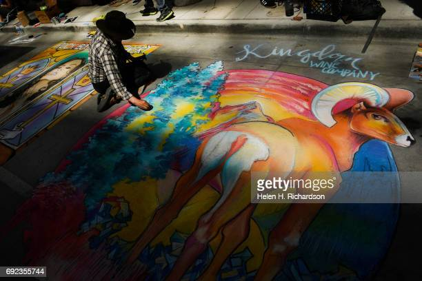 Artist Katie Vuletich works on her chalk artwork which she said was either Colorful Colorado or Big Horn Butt during the 15th annual Denver Chalk Art...
