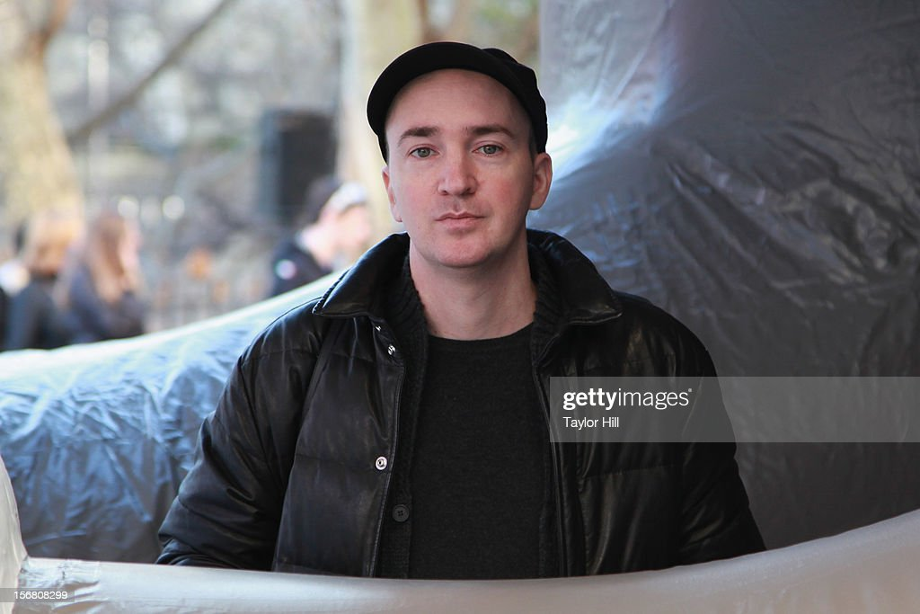 Artist KAWS poses in front of his balloon 'Companion' at the 86th Annual Macy's Thanksgiving Day Parade's 'Inflation Eve' on November 21, 2012 in New York City.