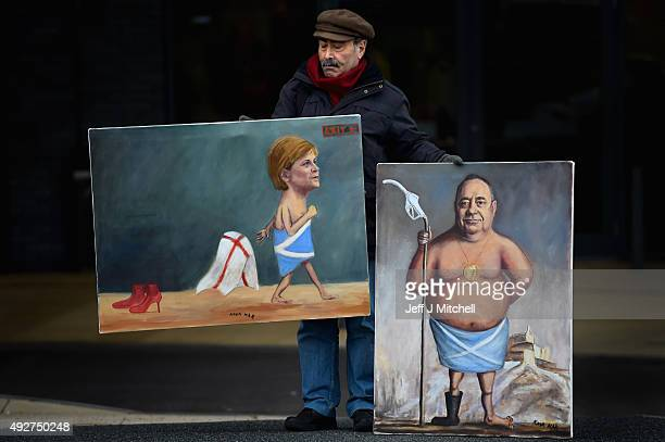 Artist Kaya Mar holds his paintings of First Minister Nicola Sturgeon and Alex Salmond MP outside the 81st SNP conference at the Aberdeen Exhibition...