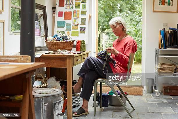 Artist knitting in her studio