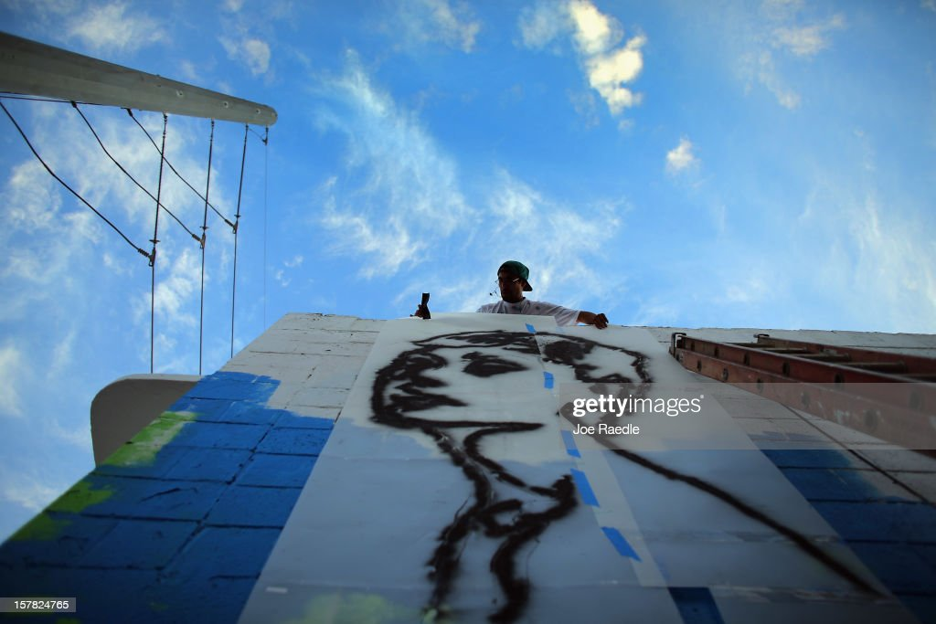 "Artist known as Free Humanity works on his painting on the wall of a building as he participates in the Wynwood Walls art project on December 6, 2012 in Miami, Florida. The art project along with many other satellite shows around the city coincide with the International art show, ""Art Basel"", which runs until the 9th of December."