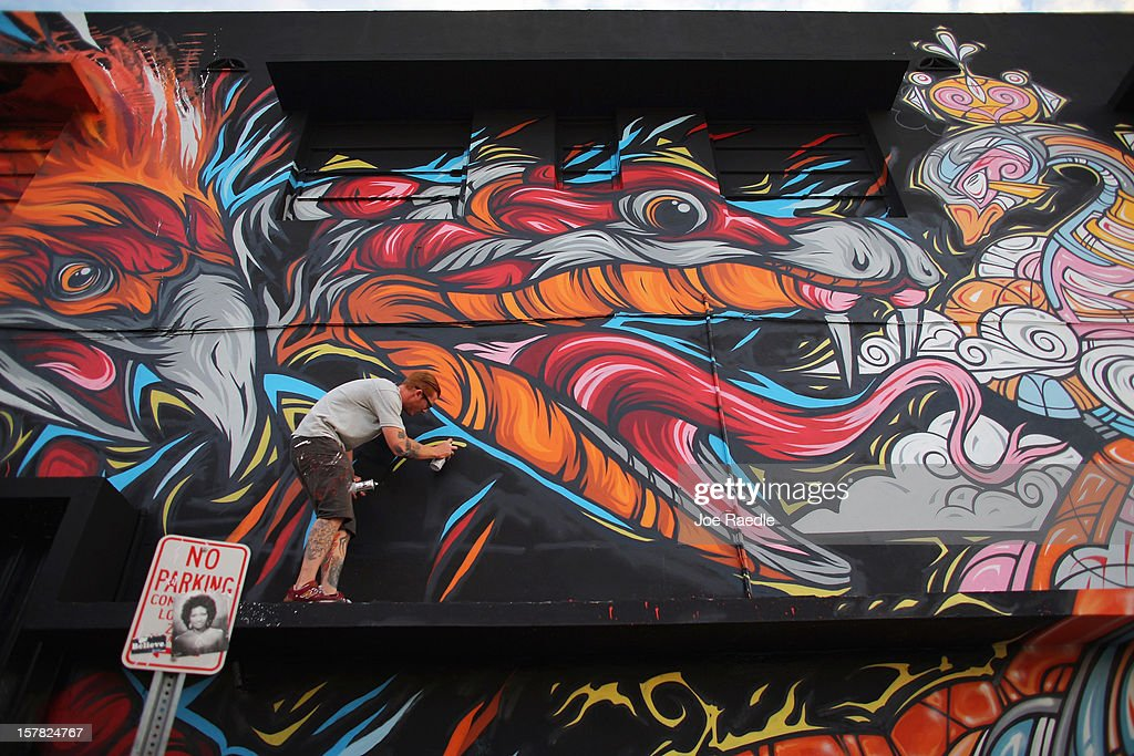Artist known as Meggs paints on the wall of a building as he participates in the Wynwood Walls art project on December 6, 2012 in Miami, Florida. The art project along with many other satellite shows around the city coincide with the International art show, 'Art Basel', which runs until the 9th of December.