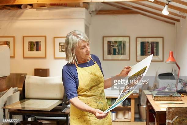 Artist looking at print in her studio
