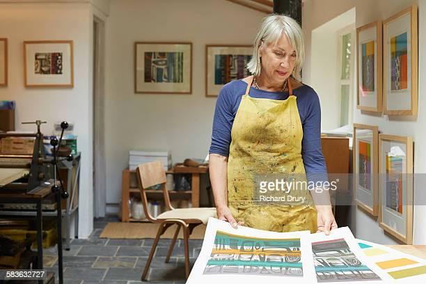Artist looking at prints in her studio