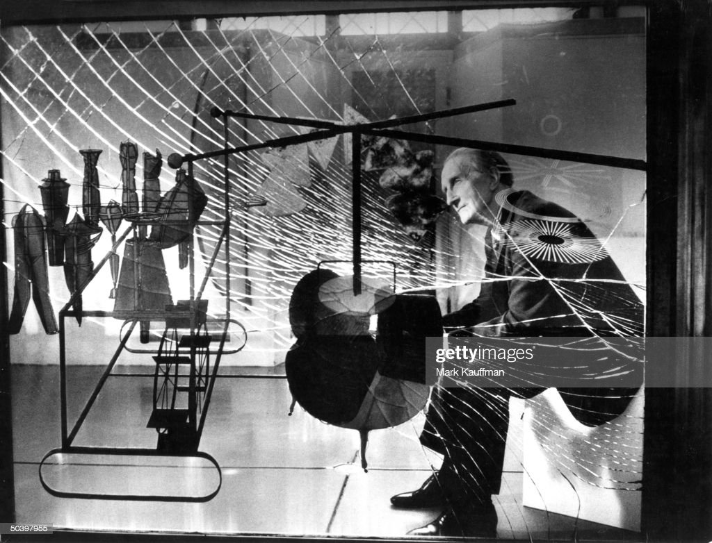 Artist <a gi-track='captionPersonalityLinkClicked' href=/galleries/search?phrase=Marcel+Duchamp&family=editorial&specificpeople=227454 ng-click='$event.stopPropagation()'>Marcel Duchamp</a> being viewed through glass of his major work The Bride Stripped Bare by Her Bachelors.''