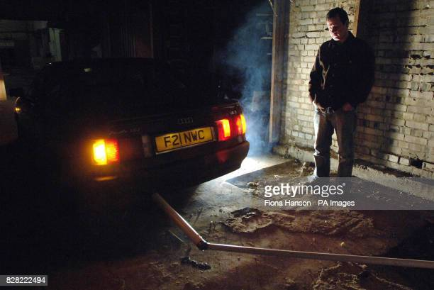 Artist Mark McGowan with a pipe connected to the exhaust of an Audi 80 which forms part of his installation The Unnecessary Journey in a car park...