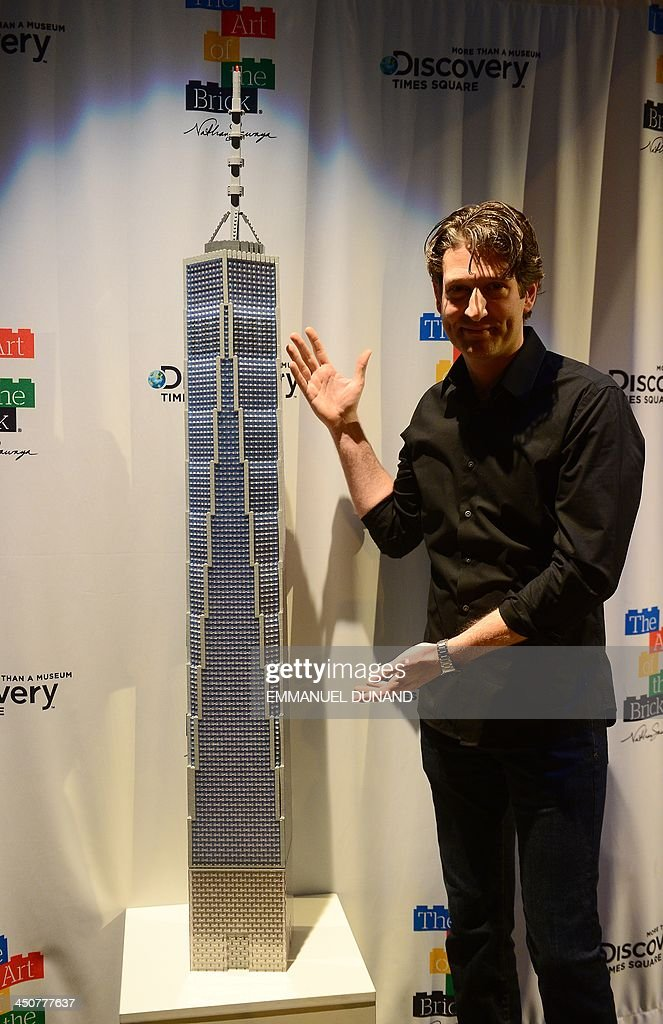 LEGO artist Nathan Sawaya poses next to a LEGO replica of One World Trade Center during its unveiling in New York, November 20, 2013. The scuplture was created by Sawaya following a contest 'What should Nathan build?' , in which he asked the public to suggest his next creation. The replica was unveiled as part of the final weeks of his exhibition 'The Art of Brick' which run until January, 5, 2014. AFP PHOTO/Emmanuel Dunand
