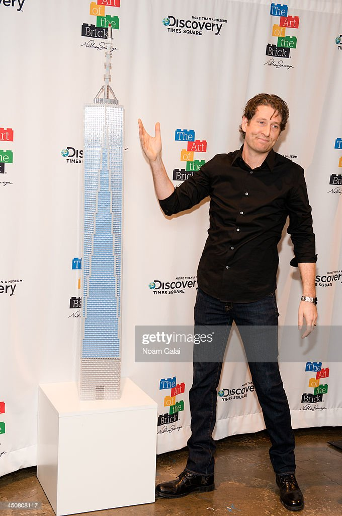 Artist Nathan Sawaya unveils a LEGO brick sculpture of the One World Trade Center building at The Art of the Brick Exhibition at Discovery Times Square Exposition Center on November 20, 2013 in New York City.