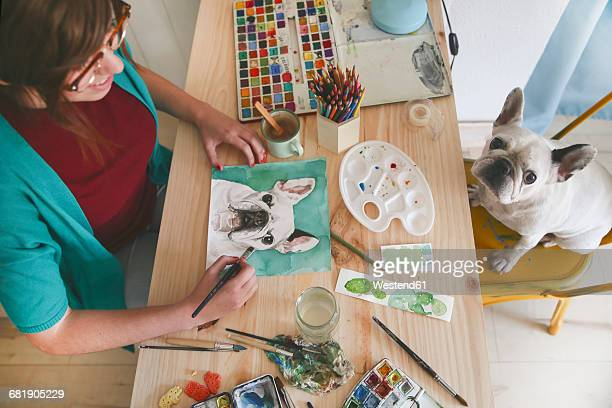 Artist painting an aquarelle of her French bulldog in her studio