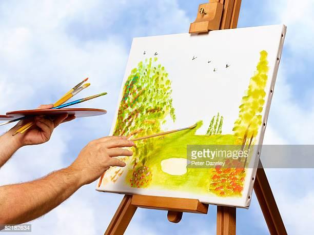 Artist Painting landscape on easel