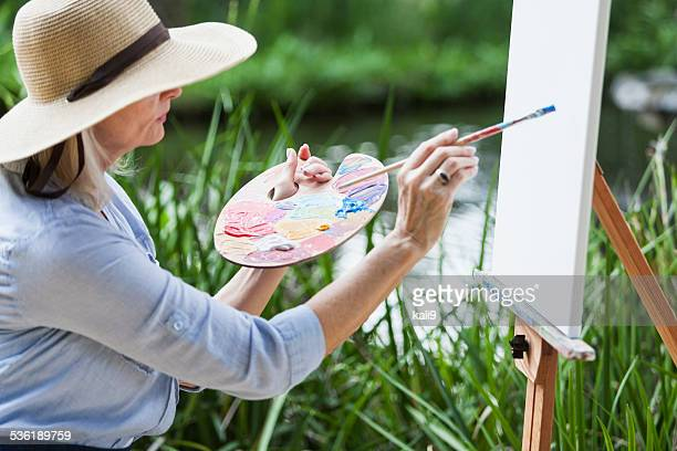 Artist painting nature on canvas