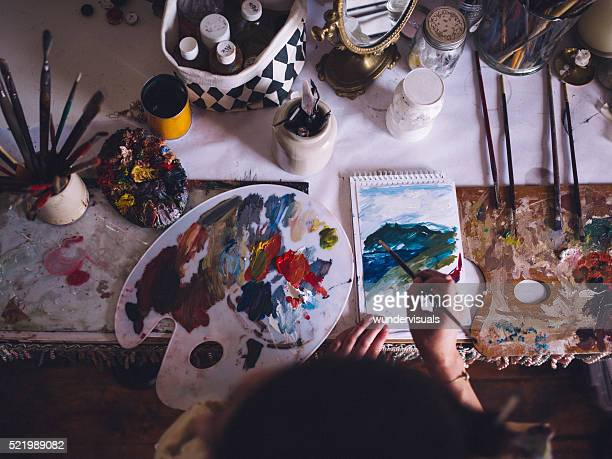 Artist painting on paper with a palette and bright colors