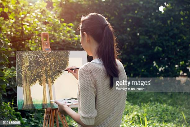 Artist painting trees outdoors
