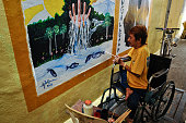 PWD artist paints a mural as he participates during the Obra sa Pader Mural Painting Competition in Makati City on Sunday The mural competition...