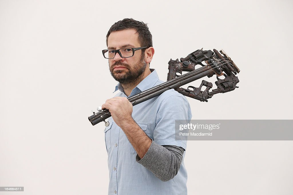 Artist Pedro Reyes holds one of his musical instruments sculpted from recycled guns at the Lisson Gallery on March 26, 2013 in London, England. Mexican artist Pedro Reyes received 6,700 destroyed weapons from the Mexican government from which he sculpted two groups of instruments. The first, a series titled Imagine, is an orchestra of fifty instruments, from flutes to string and percussion instruments, designed to be played live. The second, Disarm, is an installation of mechanical musical instruments, which can either be automated or played live by an individual operator using a laptop computer or midi keyboard.