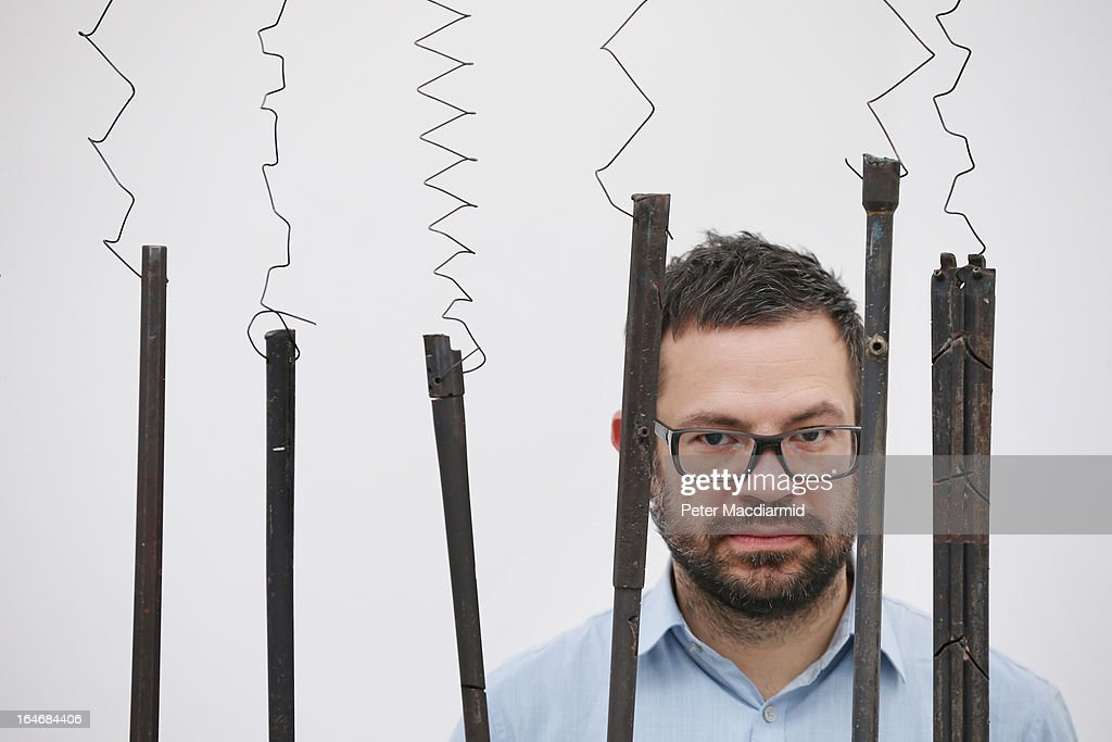 Artist Pedro Reyes stands behind one of his musical instruments sculpted from recycled guns at the Lisson Gallery on March 26, 2013 in London, England. Mexican artist Pedro Reyes received 6,700 destroyed weapons from the Mexican government from which he sculpted two groups of instruments. The first, a series titled Imagine, is an orchestra of fifty instruments, from flutes to string and percussion instruments, designed to be played live. The second, Disarm, is an installation of mechanical musical instruments, which can either be automated or played live by an individual operator using a laptop computer or midi keyboard.