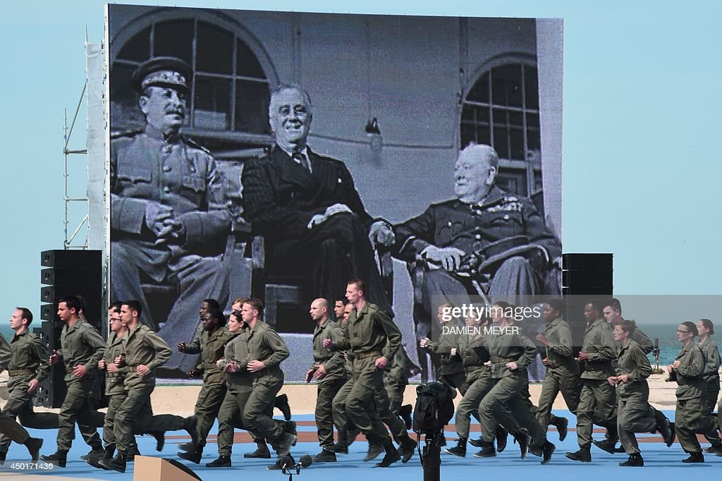 Artist perform on the beach of Ouistreham as late former British Prime Minister Winston Churchill (R), late former US president Franklin Roosevelt and late former Soviet leader Joseph Stalin (L) are pictured on a giant screen during the international D-Day commemoration ceremony in Normandy, on June 6, 2014, marking the 70th anniversary of the World War II Allied landings in Normandy.