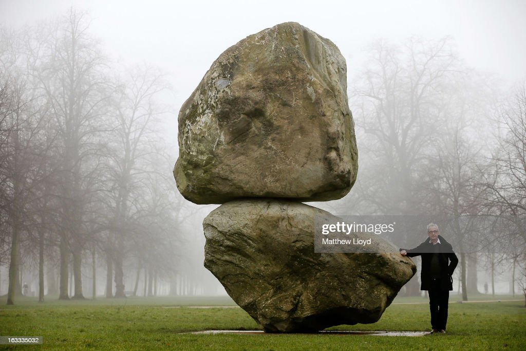 Artist Peter Fischli poses next to 'Rock on Top of Another Rock', in Hyde Park on March 8, 2013 in London, England. The piece, commissioned by the Serpentine Gallery, was created by the artistic duo Fischli/Weiss, and was one of the last works they jointly conceived before David Weiss's death last year.