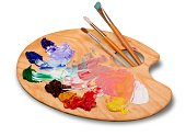 Wooden art palette with blobs of paint and a brushes on white background
