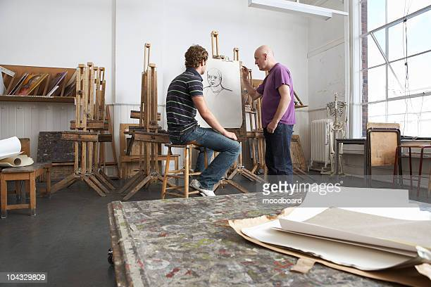 Artist pointing out detail of charcoal portrait, art student looking on