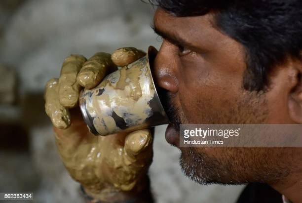 Artist Ramesh having tea holding the glass with mud smeared hand while making earthen lamps in his hut at Pottery Town on October 12 2017 in...