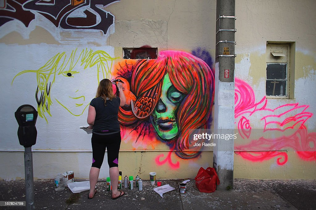 Artist, Sarah Ballard, works on her painting on the wall of a building as she participates in the Wynwood Walls art project on December 6, 2012 in Miami, Florida. The art project along with many other satellite shows around the city coincide with the International art show, 'Art Basel', which runs until the 9th of December.