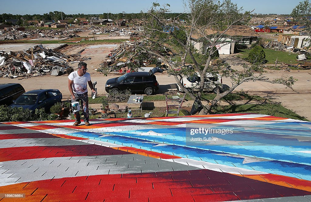 Artist Scott LoBaido of Staten Island, New York, paints an American Flag on the roof of a home damaged by a tornado June 2, 2013 in Moore, Oklahoma. Residents of Moore, Oklahoma continue to recover and sift through the remains of their homes two weeks after a devastating EF-5 tornado ripped through the town killing 24 people and destroying hundreds of homes and businesses.