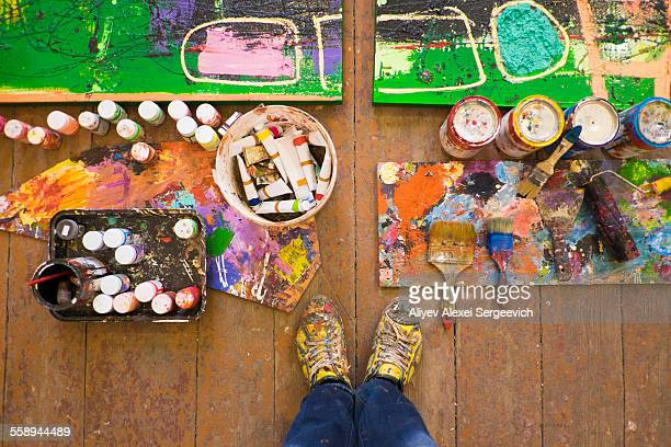 Artist selfie of feet paints and abstract painting in studio