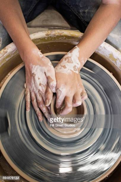Artist shaping pottery on wheel