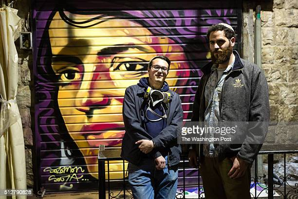 Artist Solomon Souza and Berel Hahn who came up with the idea to paint over shutters at the Jerusalem market pose for a photograph in front of...