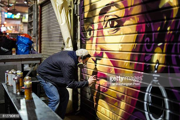 Artist Solomon Souza is seen as he spraypaints a portrait depicting IsraeliArab news anchor Lucy Aharish over a closed shutter at the Mahane Yehuda...