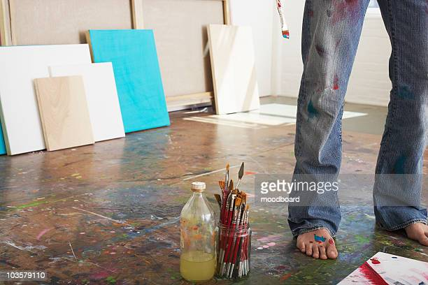 Artist standing by paint brushes and paint thinner in studio, low section