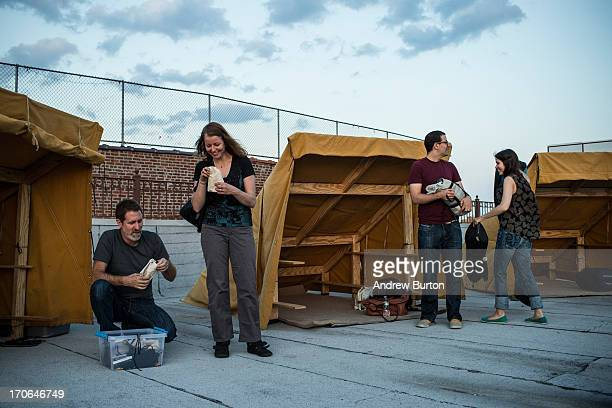 Artist Thomas Stevenson far left hands campers toolkits while camping on an undisclosed rooftop on June 15 2013 in the Brooklyn Borough of New York...