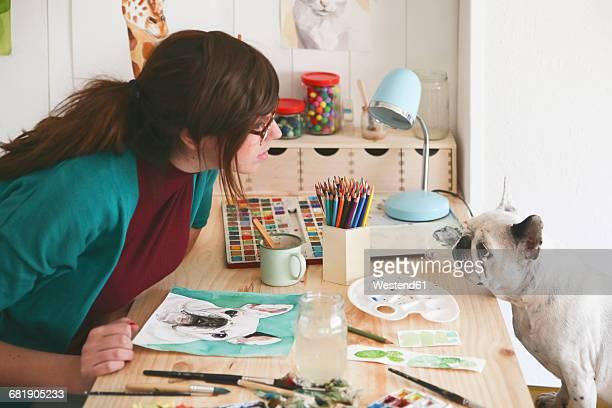 Artist watching French bulldog in her studio