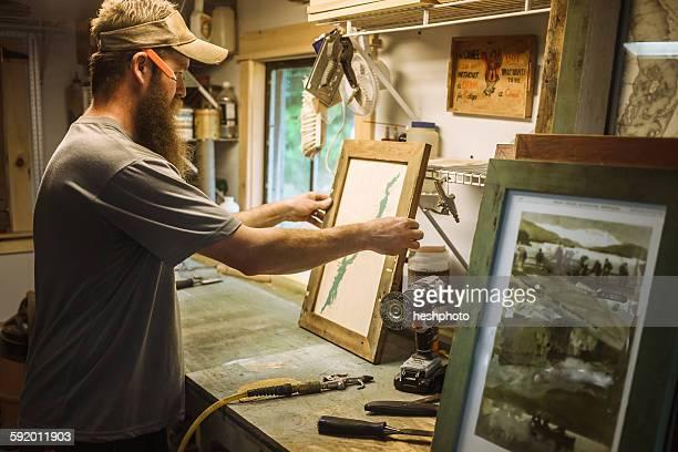Artist working in workshop, framing artwork
