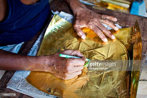 Artist working with copper sheet at market in Puthu Mandapam.